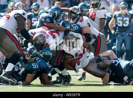 Tampa Bay Buccaneers running back Michael Pittman (32) is tackled by Seattle Seahawks defensive tackle Craig Terrell (R) in the third quarter at Qwest Field in Seattle on September 9, 2007. The Seahawks beat the Buccaneers 20-6 in their season opener. (UPI Photo/Jim Bryant) - Stock Photo