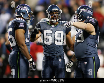 Seattle Seahawks'  linebacker Julian Peterson (C) talks with defensive tackles Ellis Wyms (L) and Craig Terrill (R) during a timeout in the fourth quarter at Qwest Field in Seattle on November 12, 2007. The Seahawks beat the 49ers 24-0. (UPI Photo/Jim Bryant) - Stock Photo