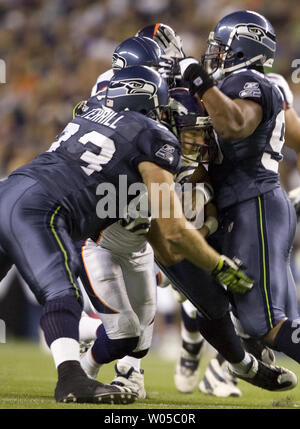 Denver Broncos quarterback Tom Brandstater (C) is sacked by Seattle Seahawks'  Craig Terrill (93), Michael Bennett (R) and David Hawthorne in the fourth quarter at Qwest Field in Seattle on August  22, 2009.   The Seahawks defense registered four sacks in their 27-13 win over the Broncos.     UPI /Jim Bryant) - Stock Photo