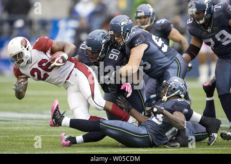 Arizona Cardinals running back Beanie Wells dive for extra yardage before being tackled by Seattle Seahawks defenders, Chris Cole, Craig Terrill and MArcus Trufant in the second quarter on Sunday  October 24, 2010 at Qwest Field in Seattle.  The Seahawks took advantage of five Arizona turnovers in a 22-10 win over the Cardinals on Sunday.     (UPI Photo/Jim Bryant) - Stock Photo