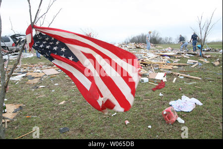 An American flag tied from a tree, flys in the wind on March 12, near a home that was destroyed by a tornado while volunteers sift through debris in Perry County near the small town St. Mary about 80 miles south of St. Louis on March 11. Two people were killed when a man and a woman were traveling in a car and the strong winds pushed the car 75 yards off the road into a propane storage tank. Seventeen others in the small community were injured. Several tornados in a 30 square mile area, landed in communities in Missouri and Illinois.   (UPI Photo/Bill Greenblatt) - Stock Photo