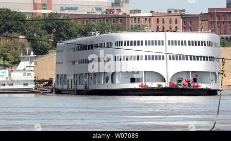 The Admiral riverboat is helped turning around on the Mississippi River by the tugboat Michael Luhr as it leaves its port in St. Louis on July 19, 2011. The Admiral is being pushed to Columbia, Illinois where it will be cut up for scrap. The Admiral was once recorded as being the largest river cruise ship in the world and the first Mississippi Riverboat to be fully air-conditioned. In the 1990's the Admiral became a riverboat casino, known as the 'President Casino on the Admiral', which went out of business last year. The Admiral has been a fixture on the St. Louis riverfront since 1937. - Stock Photo