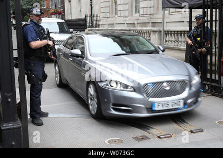 London, UK. 26th June, 2019. Armed police on the gates of Downing Street watch as British Prime Minister Theresa May is driven out at speed on her way to Prime Ministers Questions in Westminster, London, UK on June 26, 2019. Credit: Paul Marriott/Alamy Live News - Stock Photo