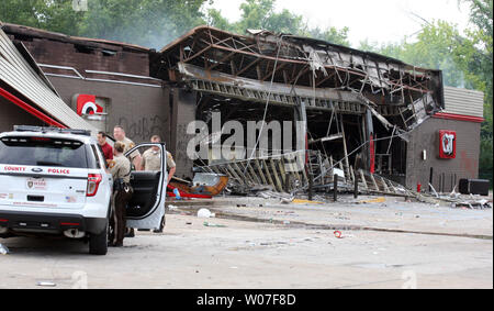 St. Louis County Police stand guard at a QuikTrip Gas station following a night of looting, rioting and arsons in Ferguson, Missouri on August 11, 2014. People are upset because of the Ferguson Police shooting and death of an unarmed black teenager Michael Brown on August 9, 2014. In all about 20 businesses sustained damage after a candlelight vigil turned violent.   UPI/Bill Greenblatt