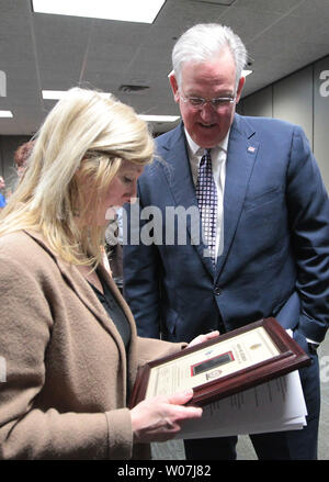 Missouri Governor Jay Nixon and Nancy Laubenthal, General Motors Wentzville Plant Manager look at the award given to the plant in Wentzville, Missouri on March 9, 2015. Nixon presented General Motors with a Flag of Freedom award, recognizing the company's commitment to hiring veterans through Missouri's Show-Me Heroes program.The Flag of Freedom Award, which consists of a plaque featuring an American flag patch from the combat uniform of a member of the Missouri National Guard worn while that citizen-Soldier or Airman was deployed in Iraq or Afghanistan. Photo by Bill Greenblatt/UPI - Stock Photo