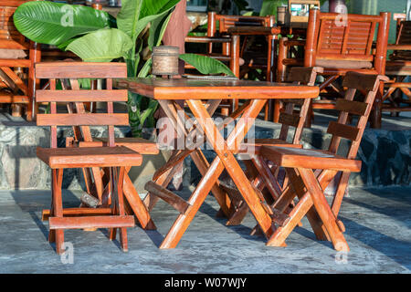 Wooden table and chairs in empty cafe next to beach. Close up. Island Koh Phangan, Thailand - Stock Photo