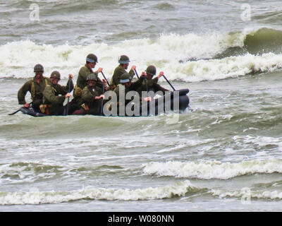 UTAH, FRANCE - June 06, 2019. Special forces men in camouflage uniforms paddling army kayak. Boat moving across the sea, diversionary mission for D-Da - Stock Photo