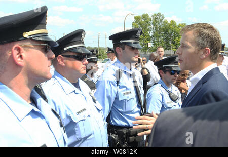 Missouri Governor Eric Greitens talks with St. Louis Police officers afer unveiling a new program that with deal with the violence problem in St. Louis during a press conference in St. Louis on July 10, 2017. The state of Missouri will be joining the FBI and DEA's Mission Save task force—which is focused on reducing violence by targeting the most violent offenders. A Special Operations Unit of the Missouri State Highway Patrol  will assist local law enforcement to suppress violent crime on highways. St. Louis has experienced 101 murders so far this year, many resulting from rolling gun battles