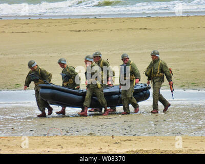 UTAH, FRANCE - June 06, 2019. Special forces men in camouflage uniforms out army kayak on beach. Diversionary mission for D-Day 75 birthday, end of wo - Stock Photo