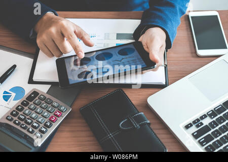 Businessman hands using text information on digital tablet to analyze financial statistical chart data and calculate cost of investment project. - Stock Photo