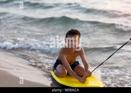Young boy body boarding fearlessly in shallow waves - Stock Photo