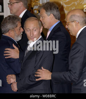 Russian President Vladimir Putin (L) looks back at Atomic Energy Agency Director-General Mohamed ElBaradei after a G8 leaders group photo following the final session of the G8 Summit in Saint Petersburg, Russia on July 17, 2006. (UPI Photo/Dima Volgin) - Stock Photo