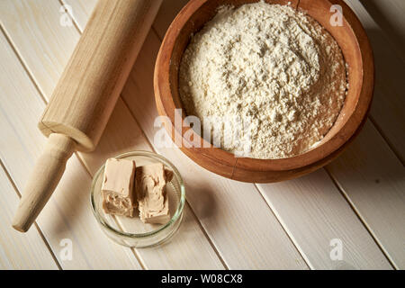 Top view of bowl of flour with yeast and rolling pin on  white  kitchen table - Stock Photo