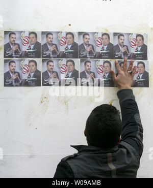An Iranian man pastes up  posters of two  parliamentary candidates in Tehran, Iran on February 25, 2012.  Iranians prepare themselves for upcoming election on March 2, 2012. The Guardian Council has approved the eligibility of 3,400 candidates for the parliamentary elections.   UPI/Maryam Rahmanian - Stock Photo