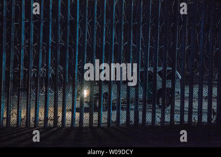 Looking through the border fence from Las Playas de Tijuana, Mexico, US Customs and Border Patrol SUV sits in front of the border fence covered in concertina wire in San Ysidro, California on December 9, 2018.     Photo by Ariana Drehsler/UPI - Stock Photo