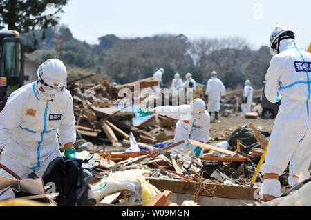 Japanese police wearing chemical protection suits search for victims inside the 20 kilometer radius around the Fukushima Dai-ichi nuclear power plant in Minamisoma, Fukushima prefecture, Japan, on April 15, 2011. A massive earthquake and ensuing tsunami on March 11 destroyed homes, killed thousands and caused a nuclear disaster.    UPI/Keizo Mori - Stock Photo