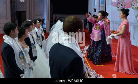 Hak Ja Han, wife of late Unification Church founder Sun Myung Moon sprinkles the holy water onto newly married couples during a Blessing Ceremony of the Family Federation for World Peace and Unification at the CheongShim Peace World Center in Gapyeong, South Korea, on February 20, 2016.     Photo by keizo Mori - Stock Photo