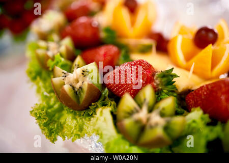 Fresh, exotic, organic fruits, light snacks in a plate on a buffet table. Strawberries in a glass bowl on the white table. - Stock Photo