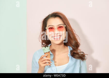 summer, junk food and people concept - young woman or teenage girl in sunglasses eating ice cream - Stock Photo