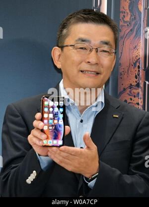 Makoto Takahashi, President of KDDI Corporation poses for camera during launch event for Apple New iPhone Xs and Xs Max at the KDDI's au Shinjuku store in Tokyo, Japan, on September 21, 2018.     Photo by Keizo Mori/UPI - Stock Photo