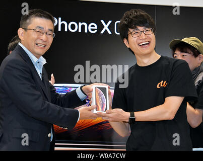 Makoto Takahash(L)i, President of KDDI Corporation and first customer pose for camera during a launch event for Apple New iPhone Xs and Xs Max at the KDDI's au Shinjuku store in Tokyo, Japan, on September 21, 2018.     Photo by Keizo Mori/UPI - Stock Photo