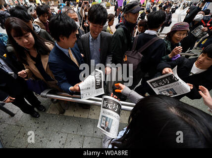 People receive the extra edition of newspaper reporting about the new era name 'Reiwa' near the Akihabara station in Tokyo, Japan on April 1, 2019. Japan's Chief Cabinet Secretary Yoshihide Suga said the new era name 'Reiwa' is derived from the 'Manyoshu' the oldest anthology of Japanese poetry.    Photo by Keizo Mori/UPI - Stock Photo