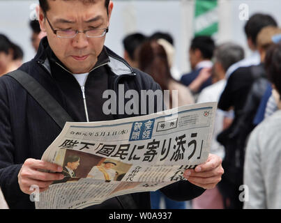 People receive the extra edition of newspaper reporting about the new emperor Naruhito ascends enthroned the Chrysanthemum Throne near the Shinbashi station in Tokyo, Japan on May 1, 2019.     Photo by Keizo Mori/UPI - Stock Photo