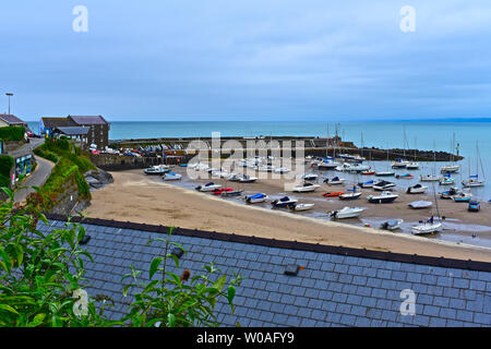 An overview of the pretty little harbour at Newquay in West Wales, at low tide.Sandy beach and stone breakwater.Assorted leisure craft & fishing boats - Stock Photo