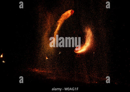 Fire show, dancing with flame, male master juggling with fireworks, performance outdoors, draws a fiery figure in the dark, bright sparks in the night - Stock Photo