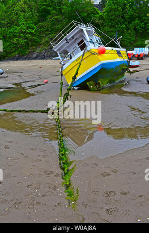 A fishing boat lies on it's side at low tide in Newquay harbour in West Wales. A seaweed encrusted chain stretches to boat over the sand. - Stock Photo