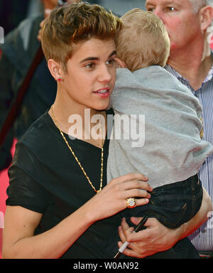 Justin Bieber holds his baby brother Jaxon as he speaks to ...