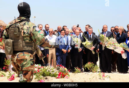 A hooded Tunisian police officer stands guard as (R to L) British Home Secretary Theresa May, Tunisian Interior minister Mohamed Najem Gharsalli, German Interior Minister Thomas de Maiziere, and French Interior Minister Bernard Cazeneuve lay flowers on the site of a shooting attack on the beach in front of the Riu Imperial Marhaba Hotel in Port el Kantaoui, on the outskirts of Sousse south of the capital Tunis, on June 29, 2015. The Islamic State (ISIS) group claimed responsibility on June 27 for the massacre in the seaside resort that killed nearly 40 people, most of them British tourists, in - Stock Photo