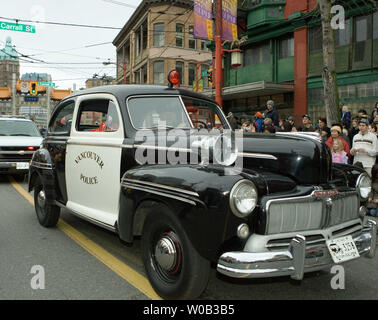 A Vancouver Police Department vintage police car joins the Chinese (Lunar) New Year parade winding through Vancouver's Chinatown, January 29, 2006. Tens of thousands of spectators attend the parade in Vancouver which has one of the largest Chinese communities in North America.  (UPI Photo/Heinz Ruckemann) - Stock Photo
