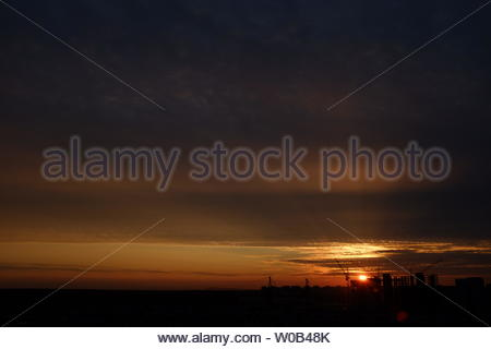 Beautiful sunset over the city. The night sky with the setting sun. - Stock Photo