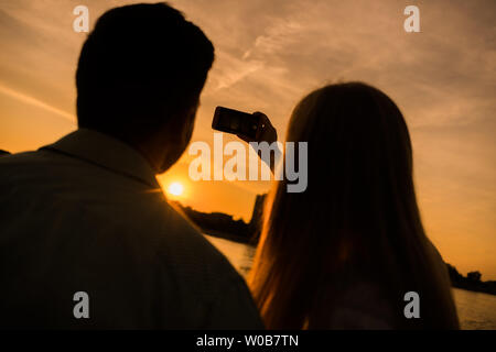 Happy couple is taking selfie in sunset in the city. - Stock Photo