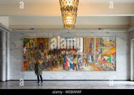 Oslo Town Hall, view of a female tourist looking at a Reidar Aulie painting titled 'The Labor Movement's Development in Oslo' in the Oslo City Hall. - Stock Photo