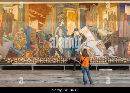 Oslo City Hall, view of two young people pictured in front of the huge Alf Rosen fresco titled The Occupation inside the Grand Hall of Oslo City Hall. - Stock Photo