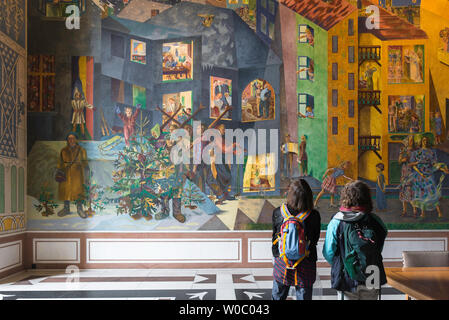 Women travel, rear view of two women with backpacks looking at the colourful Per Krohg fresco inside the East Gallery of Oslo City Hall, Norway. - Stock Photo