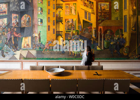 City Hall Oslo, view of a young woman walking past the colourful Per Krohg fresco inside the East Gallery of Oslo City Hall (Radhus), Norway. - Stock Photo