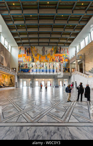 Oslo City Hall, view of tourists looking at the huge Henrik Sorensen painting inside the Great Hall in Oslo City Hall (Radhus), Norway. - Stock Photo