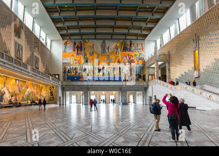 Oslo City Hall, rear view of a young woman taking a photo of the Henrik Sorensen painting inside the Great Hall in Oslo City Hall (Radhus), Norway. - Stock Photo