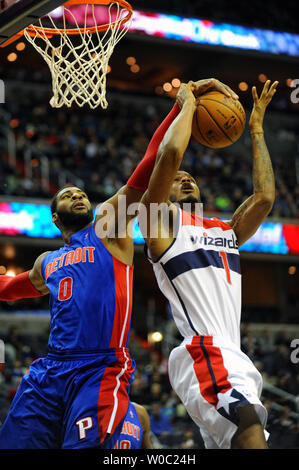 Washington Wizards small forward Trevor Ariza (1) scores and is fouled by Detroit Pistons center Andre Drummond (0) in the first half at the Verizon Center in Washington, D.C. on December 28, 2013.   UPI/Mark Goldman - Stock Photo