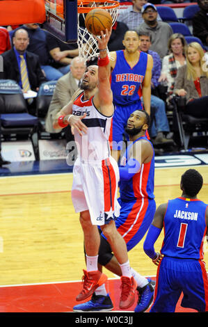 Washington Wizards center Marcin Gortat (4) scores against Detroit Pistons center Andre Drummond (0) in the first half at the Verizon Center in Washington, D.C. on February 28, 2015.   Photo by Mark Goldman/UPI - Stock Photo