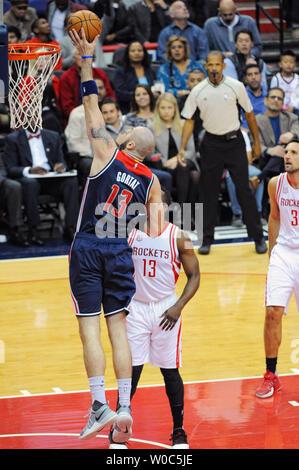 Washington Wizards center Marcin Gortat (13) scores against Houston Rockets guard James Harden (13) in the first half at the Verizon Center in Washington, D.C. on November 7, 2016.   Photo by Mark Goldman/UPI - Stock Photo