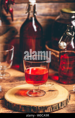 Homemade red currant liquor in a drinking glass - Stock Photo