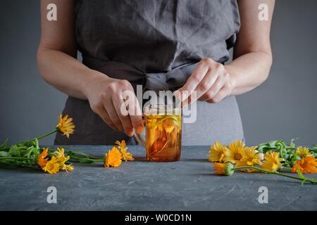 Woman making healthy tea with calendula or marigold flowers. - Stock Photo