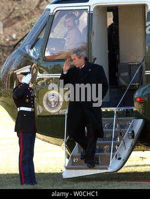 U.S. President George W. Bush salutes his Marine escort on the South Lawn of the White House as he arrives from a forum on health care at the Cleveland Clinic on Jan. 27, 2005.   (UPI Photo/Roger L. Wollenberg) - Stock Photo
