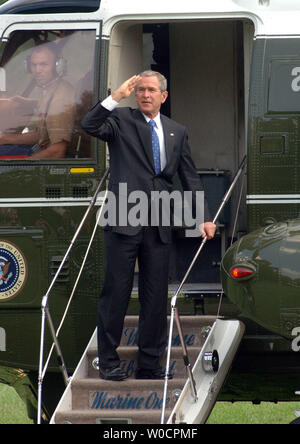 U.S. President George W. Bush salutes from the steps of Marine One on the South Lawn of the White House on Aug. 2, 2005. Bush is on his way to his Crawford, Tx., ranch for several weeks of vacation.   (UPI Photo/Roger L. Wollenberg) - Stock Photo