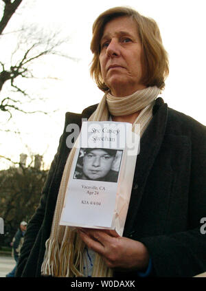 Cindy Sheehan listens to a protester read the names of 3000 American soldiers who died serving in the Iraq War while holding a paper bag with an illuminated candle outside the White House in Washington on January 3, 2007. The photograph on the bag is her son, Casey Sheehan, who died while serving in Iraq in 2004.  (UPI Photo/Alexis C. Glenn) - Stock Photo