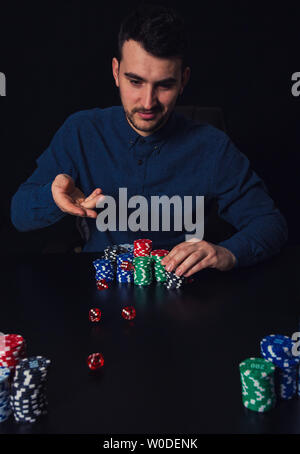 Young man gambler throwing dices seated at the casino table. Addicted guy trying luck, betting chips and gambling concept. - Stock Photo